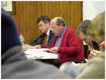 David Italiaander, center in red, testifies against the tank Wednesday night. Italiaander is flanked by attorneys Ed Bearor, left, and Steve Hinchman, right. (Photo by Ethan Andrews)